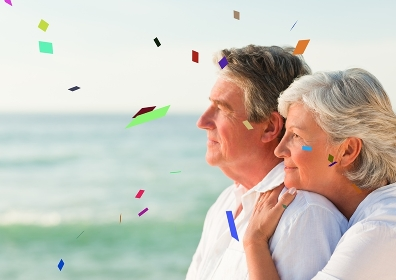 Confetti against elderly couple looking out to sea