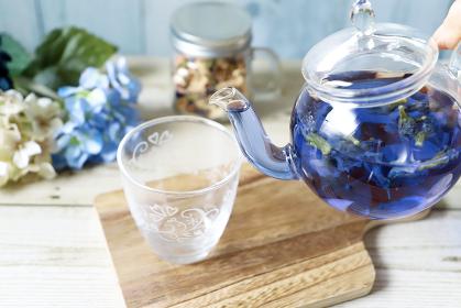 ガラスのティーポットからコップにバタフライピーとレモングラスの青いハーブティーを注ぐ様子
