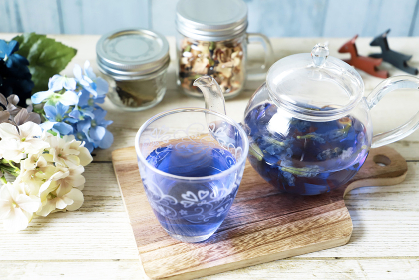 ガラスのティーポットとコップにバタフライピーとレモングラスの青いハーブティー