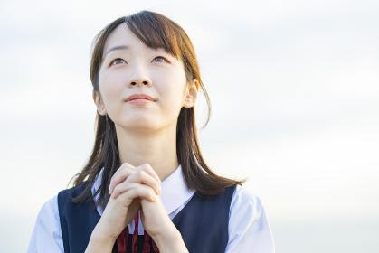 お祈りをするアジア人女性の高校生