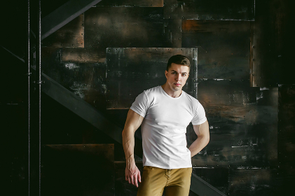 Young sexy men bodybuilder athlete, Studio portrait in a loft on the background of a stylized metal wall, a guy model in a white T-shirt and brown trousers
