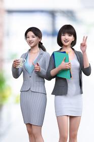 スーツを着た女性社員が2人でマグカップを持って指をさしもう1人はファイルを持ってピースサインをする