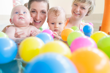 Mums and babies having fun at infant swimming course