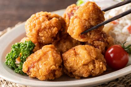 箸で挟んだ、若鶏の唐揚げのアップ