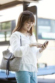 バス停でスマートフォンを操作する女性