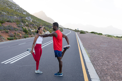 Fit african american couple in sportswear stretching on a coastal road. healthy lifestyle, exercising in nature.