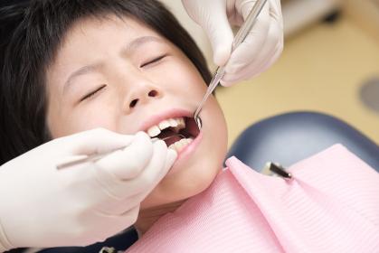 歯科検診を受ける子供:探針で虫歯を探す