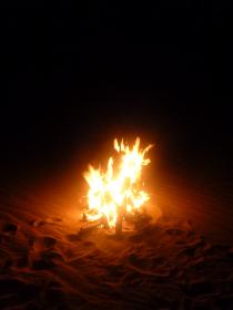 夜の砂地でのキャンプファイヤーで炎が燃える様子縦位置