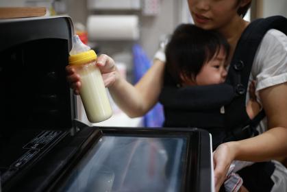 電子レンジでミルクを温めようとする母親