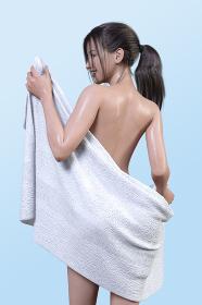 水色の背景にお風呂上がりの黒髪の女の子がバスタオルで身体を拭きながら笑顔で振り返っている