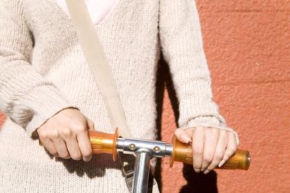 キックボードのハンドルを握る女性の手