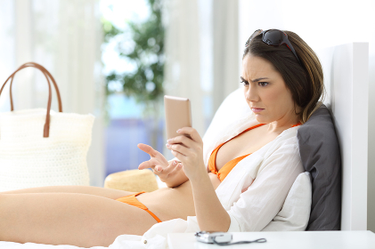 Angry hotel guest checking phone on vacation