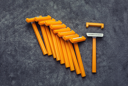 Many plastic disposable cheap shaving orange yellow razors in row