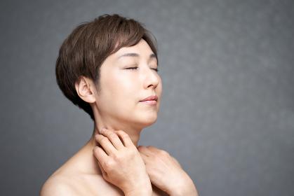首元を気にする中年の日本人女性