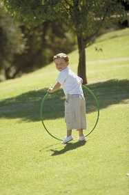 Parkszene, Portrait, Ganzfigur, 6-jaehriger Junge, bekleidet mit weissem T-Shirt, halblanger Hose und weissen Turnschuhen spielt im Spaetsommer auf einer Wiese mit einemgruenen Gymnastikreifen