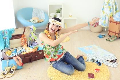 夏の旅行の準備をしながら浮かれる女性