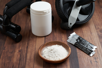トレーニング用の粉末状のサプリメントと筋トレの道具