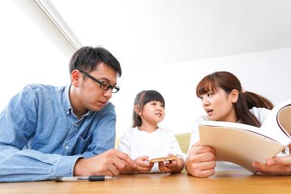 子どもに教育をする両親