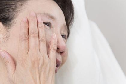 涙を流すシニア女性