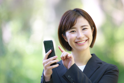 スマートフォンを持つ女性社員