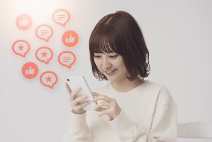 スマートフォンの画面を見る女性とSNSをイメージしたアイコン
