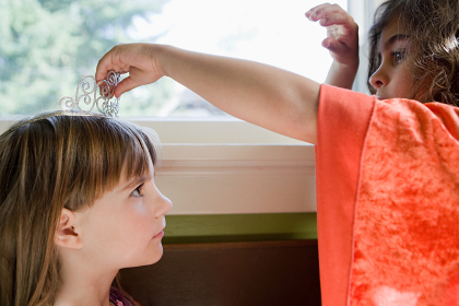 One girl putting tiara on another girl