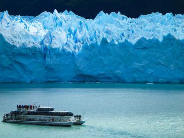 アルゼンチン・パタゴニア地方のペリトモレノにて氷河群とツアー観光客を乗せた遊覧船