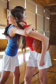 Happy female player embracing in basketball court