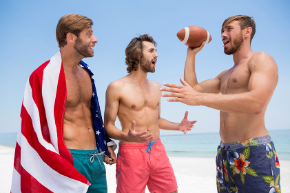 Shirtless male friends talking while standing against clear sky