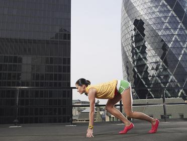 Female Runner In Start Position Against Buildings
