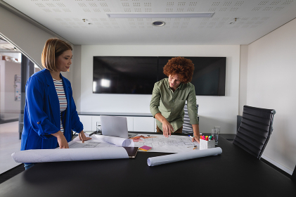 Diverse male and female colleagues in office discussing over blueprint document. independent creative design business.