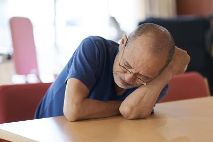 介護施設でふさぎ込む高齢者