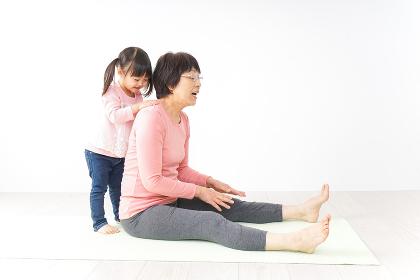 体操をするシニア女性と孫