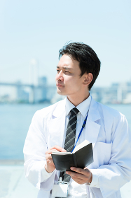 手帳を持って悩む医師