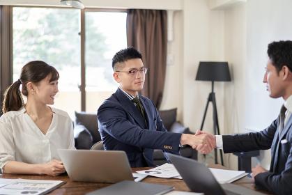 ラテン人と握手をするアジア人ビジネスマン