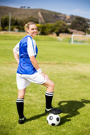 Portrait of female football player standing with her feet on ball