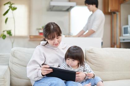 家事をするパパと子守をするアジア人のママ
