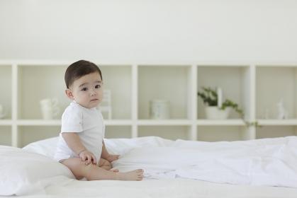 ベッドの上でお座りをする赤ちゃん
