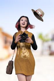 風で帽子が飛ばされつつ山吹色のパーカーワンピースを着たボブヘアで毛先がピンクのかわいらしい笑顔の女性が街中でカメラを持っている