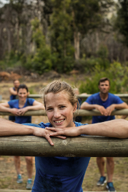 People leaning on hurdles during obstacle training