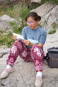A woman sitting on the rock and reading a book during weekend hiking