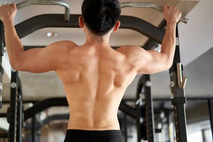トレーニングジムで懸垂をするアジア人男性