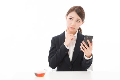スマートフォンを見る女性 ビジネス 考える
