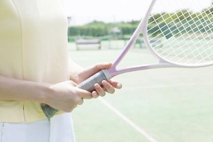 テニスラケットを持つ女性の手元
