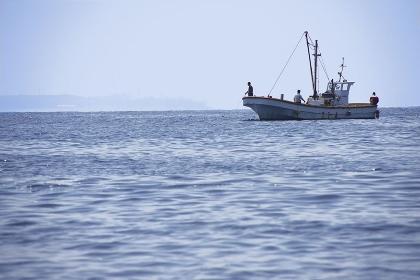 岬の沖で釣り糸を垂らす釣り船