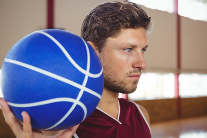 Close up of serious basketball player holding ball