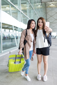 Friends taking selfie by mobile phone in airport
