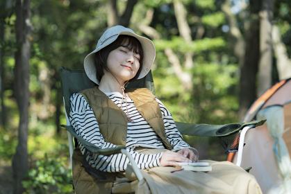 ソロキャンプイメージ・テントの前で昼寝する若い女性
