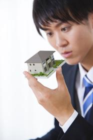 住宅模型を見る男性ビジネスマン