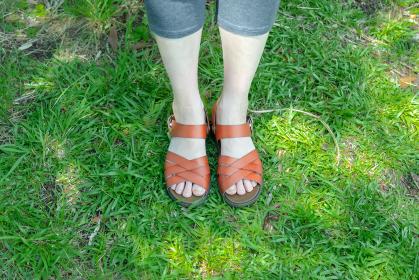 屋外 サンダルを履いた女性が足をそろえている